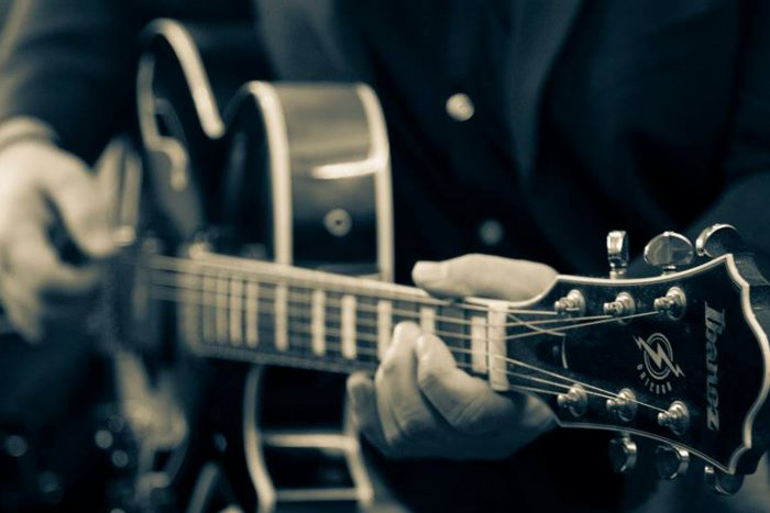 manos tocando guitarra